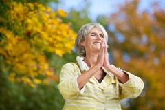 senior woman with hands clasped meditating in park - stock photo