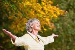 Senior woman enjoying nature in park Stock Photos