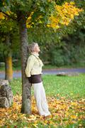 senior woman leaning on tree trunk in autumn at park - stock photo