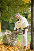 senior woman wearing shoe in autumn at park - stock photo