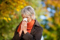 senior woman suffering from cold in park - stock photo
