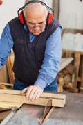 man wearing red ear protectors while using table saw - stock photo