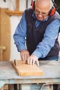 Carpenter wearing ear protectors while using table saw Stock Photos