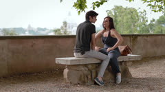 A young man and woman on a bench and talk and laugh - having a fun Stock Footage
