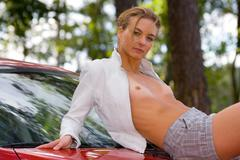 the girl on hood of the sports car - stock photo