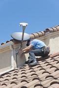 Satellite installer on roof 3. Stock Photos