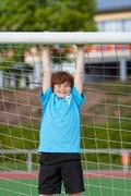 teenage boy hanging on soccer goal - stock photo