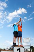 Boys holding trophy while standing on winners podium against sky Stock Photos