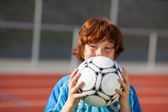 laughing boy hidden behind soccer ball - stock photo