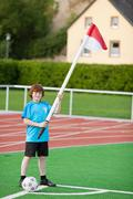 Boy with soccer ball holding flag while standing at corner Stock Photos