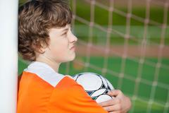 Boy holding soccer ball while leaning on net pole Stock Photos
