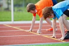 Young runners on starting position at racetrack Stock Photos