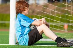 sad looking boy leaning at goal - stock photo