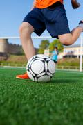 boy kicking soccer ball on field - stock photo
