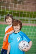 two young players in front of soccer goal - stock photo