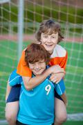 Boy giving piggyback ride to friend on soccer field Stock Photos