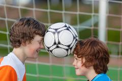 Two friends balancing soccer ball between heads Stock Photos