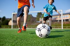 Boys playing football on field Stock Photos
