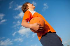basketball player holding ball against sky - stock photo