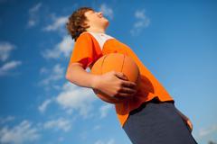 Basketball player holding ball against sky Stock Photos