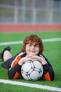 little boy with soccer lying on field - stock photo