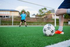 boy kicking soccer ball with goalkeeper in background - stock photo