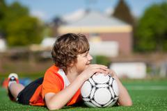 boy with soccer lying on field while looking away - stock photo