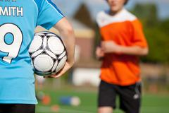 boy holding soccer ball with friend running in background - stock photo