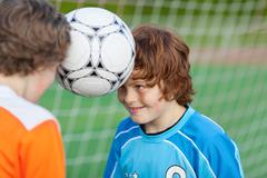 Boys balancing soccer ball with heads against sky Stock Photos