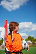 Boy holding soccer ball while looking away at corner flag Stock Photos
