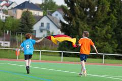 Boys celebrating while running with german flag on field Stock Photos