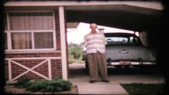 Old folks pose for camera in front of their home, 307 vintage film home movie Stock Footage