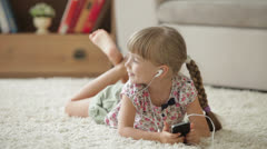 Cute little girl lying on floor listening to music on mp3 player and smiling  Stock Footage