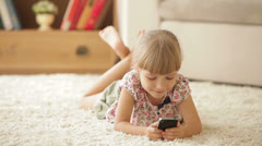 Cheerful little girl lying on carpet using mobile phone and smiling at camera - stock footage