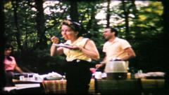 304 - family members fill their plates at picnic - vintage film home movie Stock Footage