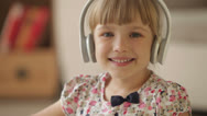 Stock Video Footage of Pretty little girl in headphones waving her hand and smiling at camera