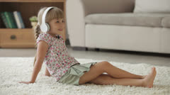 Beautiful little girl sitting on floor in living room listening to music  - stock footage