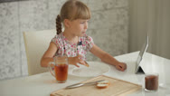 Stock Video Footage of Beautiful little girl sitting at kitchen table eating chocolate sandwich