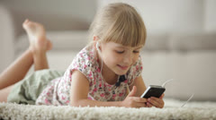 Pretty little girl lying on carpet listening to music on mp3 player and smiling - stock footage