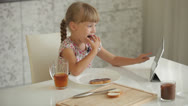 Stock Video Footage of Pretty little girl sitting at kitchen table eating chocolate sandwich and using