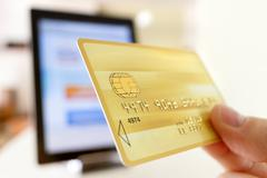 Hand holding plastic credit card on tablet pc background - stock photo