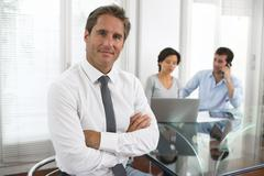 Successful business man standing with his staff in background at office Stock Photos