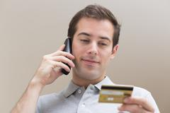 Stock Photo of Man paying with credit card on phone