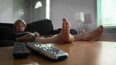 Pre-teen boy sits on couch playing video games with remote control Stock Footage
