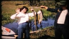 323 - fishergirl is very proud of her catch - vintage film home movie Stock Footage