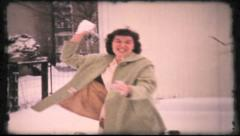 Woman throws snowballs at camera, 317 vintage film home movie Stock Footage
