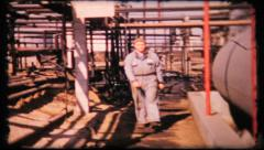 Oil refinery worker walks to camera, 320 vintage film home movie Stock Footage