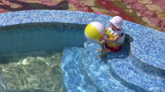 The little girl plays with a ball in water pool Stock Footage