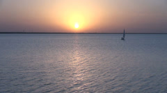 A sailboat sunset on a peaceful lake s4 Stock Footage