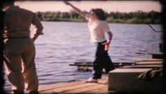 326 - woman tries casting from fishing dock - vintage film home movie - stock footage